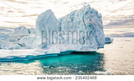 Iceberg aerial footage - giant icebergs in Disko Bay on greenland floating in Ilulissat icefjord from melting glacier Sermeq Kujalleq Glacier, aka Jakobhavns Glacier. Global warming and climate change