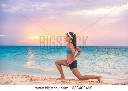 Fitness woman doing lunges exercises for glute and leg muscle workout training core muscles, balance, cardio and stability. Active girl doing front forward one leg step lunge exercise.