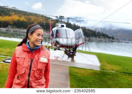 Helicopter woman tourist taking flight on tour excursion. Asian woman cruise passenger on shore activity doing helicopter ride.