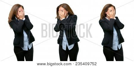 Middle age business woman smiling having shy look peeking through her fingers, covering face with hands looking confusedly broadly over white background