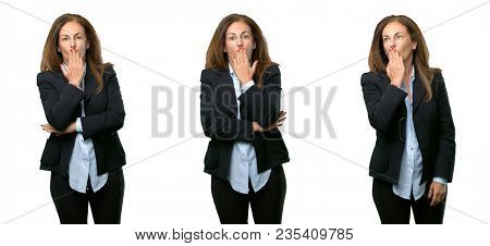 Middle age business woman covers mouth in shock, looks shy, expressing silence and mistake concepts, scared over white background