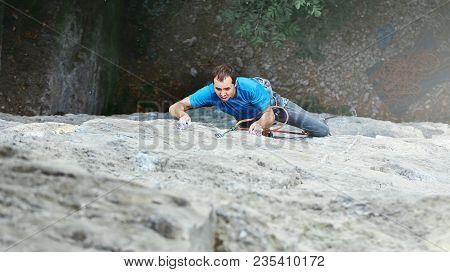 Male Rock Climber. Rock Climber Climbs On A Rocky Wall. Man Makes Hard Move. Top View