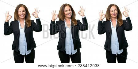 Middle age business woman doing ok sign gesture with both hands expressing meditation and relaxation over white background