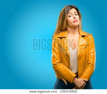 Beautiful young woman having skeptical and dissatisfied look expressing Distrust, skepticism and doubt, blue background