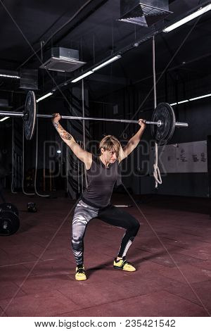 Strong Woman Lifting Barbell As A Part Of Exercise Routine. Fit Young Woman Lifting Heavy Weights At