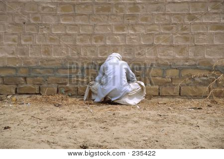 Man Seating Next To A Wall
