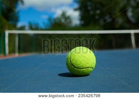 Frontview Of Yellow Bright Tennis Ball Is Lying On On Blue Carpet Of Opened Court During Sunny Day.