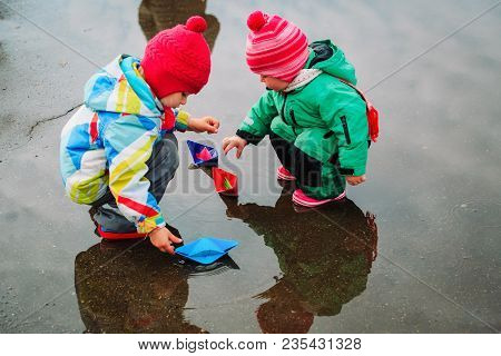 Little Girls Play With Paper Boats In Spring Water, Kids Spring Activities