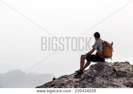 Man Hiking Silhouette In Mountains, Inspirational And Motivation Concept. Hiker With Backpack On Top