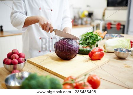 Chef of modern restaurant with sharp kitchen knife going to halve fresh purple cabbage for salad