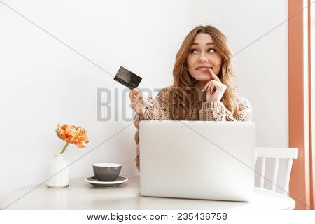 Photo of adorable brunette woman 20s in sweater thinking and holding credit card while doing payment transaction in coffee shop poster