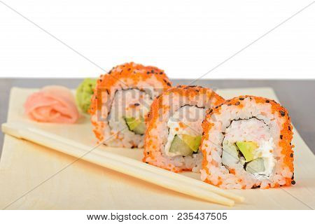 Closeup California Maki Sushi With Masago On The Wooden Plate. Roll Made Of Crab Meat, Avocado, Cucu