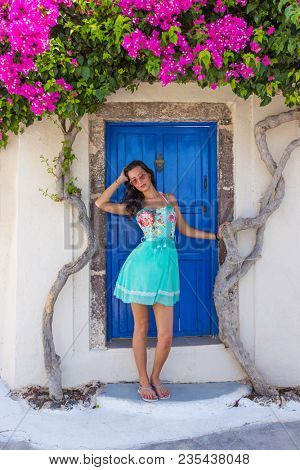 Beautiful girl in dress blooming bougenvilia with traditional old blue door in old village Emporio on the island of Santorini in Greece.