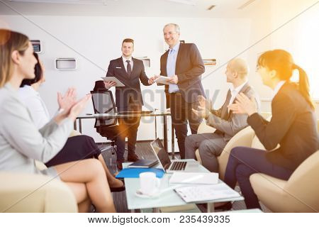 Confident businessman giving presentation while colleagues applauding during meeting in office