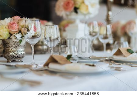 Beautiful Table Served With Glassware And Cultery, Decorated With Flowers, Prepared For Festive Even