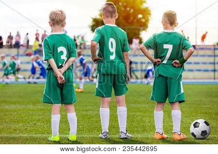 Children Football Team. Young Boys Watching Soccer Match. Football Tournament Competition In The Bac