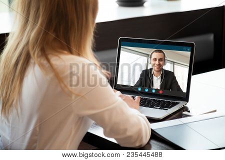 Businesswoman Making Video Call To Business Partner Using Laptop. Close-up Rear View Of Young Woman
