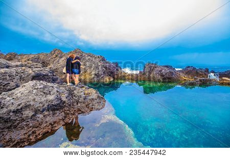 Tourists Discovering Traditional Swimming Pools Of Garachico Resort, In Tenerife Island Of Spain