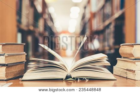 Education Learning Concept With Opening Book Or Textbook In Old Library, Stack Piles Of Literature T