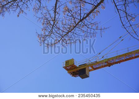 Yellow Construction Crane Isolated Against A Blue Sky Background