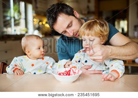 Father Feeding Two Toddlers At Home. Paternity Leave.