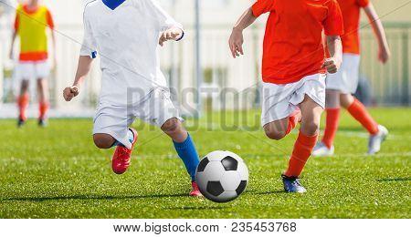 Young Soccer Football Players Running. Footballers Kicking Football Match Game. Boys Playing Footbal