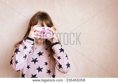 A Little Girl With A Pink Photo Camera On Pink Background. Beautiful Girl With Long Dark Blonde Hair