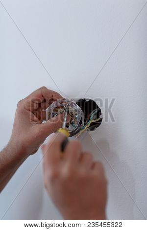 Hands Installing Light Switch With Screwdriver In Plasterboard Wall