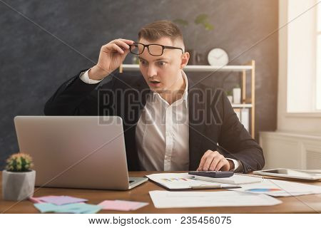 Surprised Male Financial Advisor Working With Papers And Laptop At Modern Office Interior. Shoked Ma