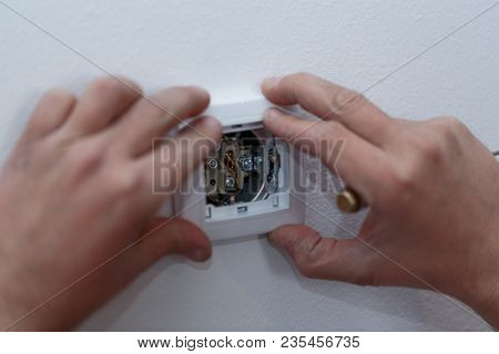Electrician Man At Work On Switches And Sockets Of A Residential Electrical System. Close Up