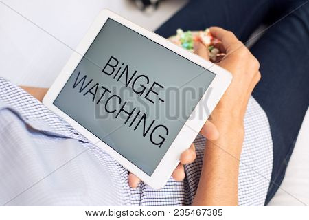 closeup of a young caucasian man lying comfortably on a couch, eating popcorn while is watching his tablet, with the text binge-watching in its screen