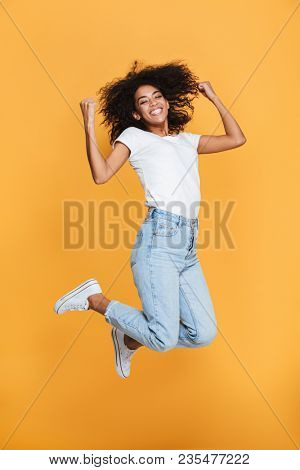 Full length portrait of a cheerful young african woman celebrating success while jumping isolated over yellow background