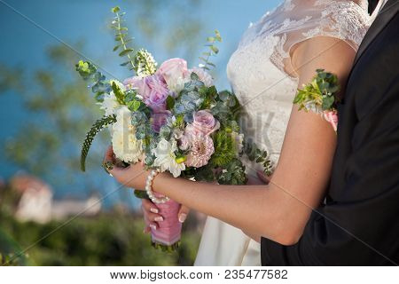 Bride And Groom With Wedding Bouquet From Roses, Eucalyptus And Dahlias, The Bride Is Dressed In Lac