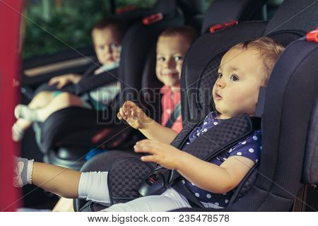 Three Children In Car Safety Seat - Family, Transport, Safety, Road Trip And People Concept
