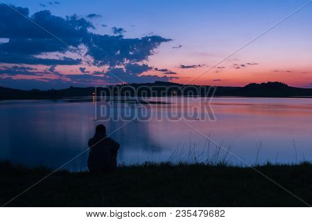 Silhouette Of Lonely Man Sitting On The River Shore In Summer After Sunset.