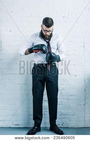 Bearded Businessman In Boxing Gloves Tying Bow Tie Against White Brick Wall