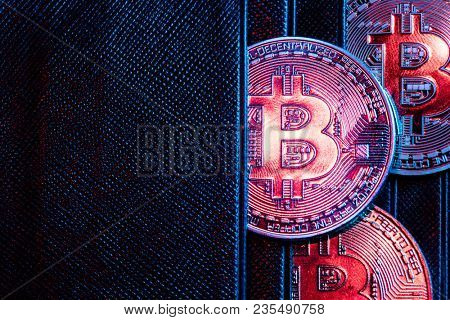 Bitcoin coins sticking out of a wallet. Cryptocurrency. Digital wallet and money.