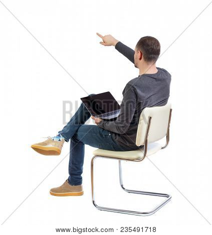 Rear view of  man who sits on a chair with a laptop and points with his hand forward.  Rear view people collection.  backside view of person.  Isolated over white background.