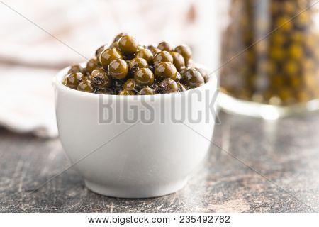 Green peppercorn in brine in bowl.