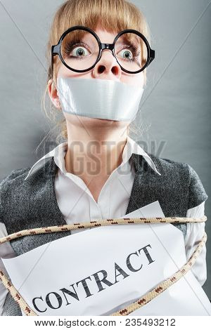 Afraid Businesswoman Bound By Contract Terms And Conditions With Mouth Taped Shut. Scared Woman Tied