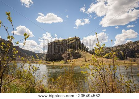Waterfront View With Rock Formations, Foliage, And Puffy Clouds In Blue Sky. Summer Day On The Misso