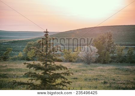 Hazy Orange Sunset Over Rolling Hills And Trees In Belt, Montana, Usa.