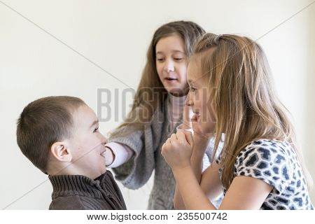 Two Little Girls Beat The Boy. Light Background. European Appearance