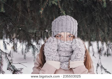 Teenage Girl With Blue Eyes And Long Hair Standing Near Pine Trees In The Forest During Cold Winter