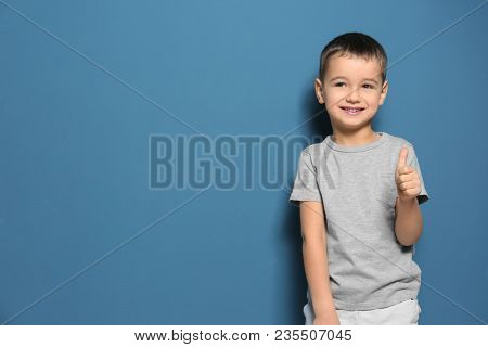 Cute little boy showing thumbup gesture on color background