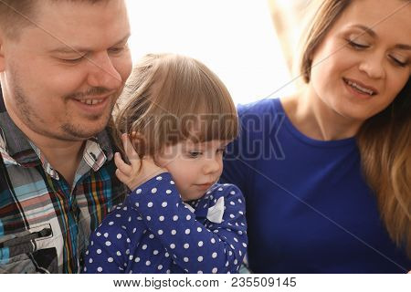 Happy Parents With Daughter At Sofa At Home. Beautiful Smiling Woman And Handsome Man Play With Cute