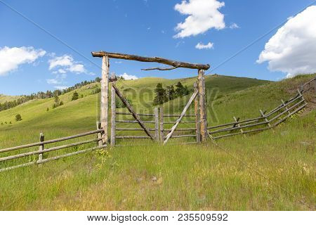 Lush, Green Landscape With Wooden Fence And Entry Gate In Remote Area Of Highwood, Montana, Usa.