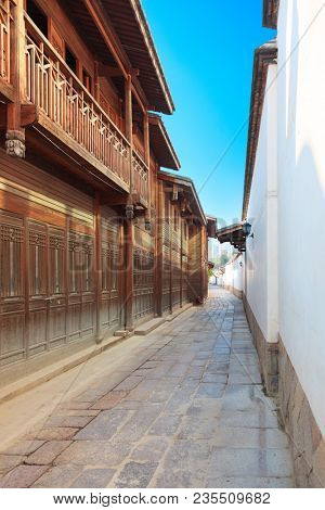 An alley with old wooden traditional Chinese house and white wall  around in Sanfang Qixiang, literally Three Lanes and Seven Alleys,a historic and cultural area in the city of Fuzhou,Fujian,China.