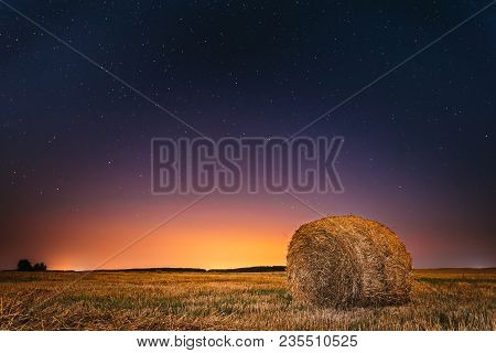 Natural Night Starry Sky Above Field Meadow With Hay Bale After Harvest. Glowing Stars And Sunset Su