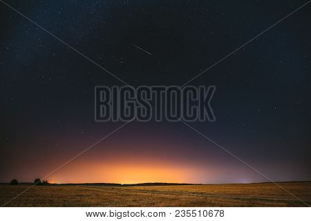 Natural Night Starry Sky Above Field Meadow. Glowing Stars, Meteorite Trail And Sunset Sunrise Light